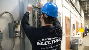 Technician Securing Cover to Electrical Panel